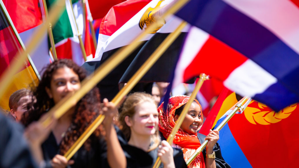 International student with country flag in procession