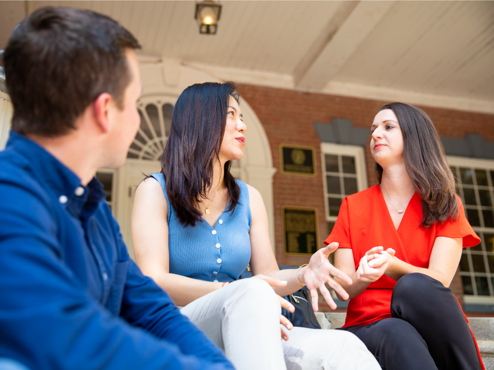 Image of three students sitting on the steps of Old North