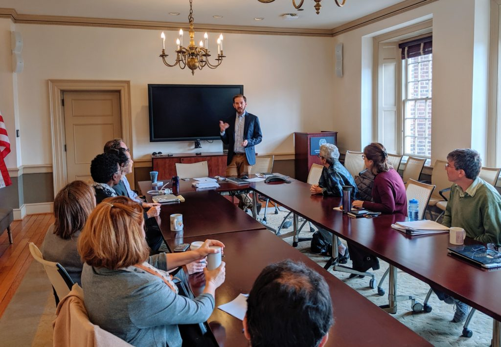 faculty attending a seminar presentation around a conference table in Old North