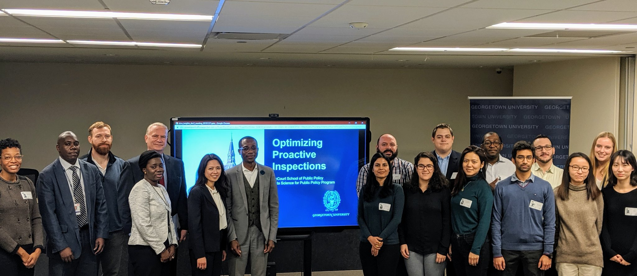 "A group of students stand by a TV monitor displaying their presentation ""Optimizing Proactive Inspections"" to McCourt faculty and the DC Department of Consumer and Regulatory Affairs"