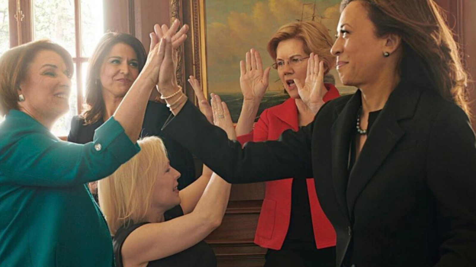 Female political leaders giving each other high-fives