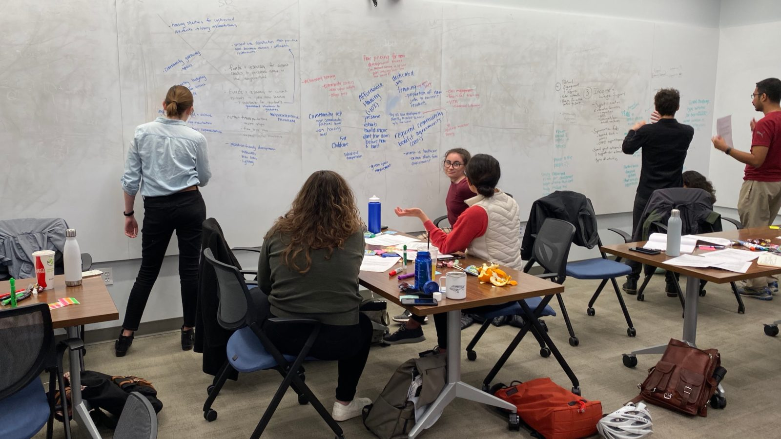 Students working in the community - seated at a table and writing items on a board