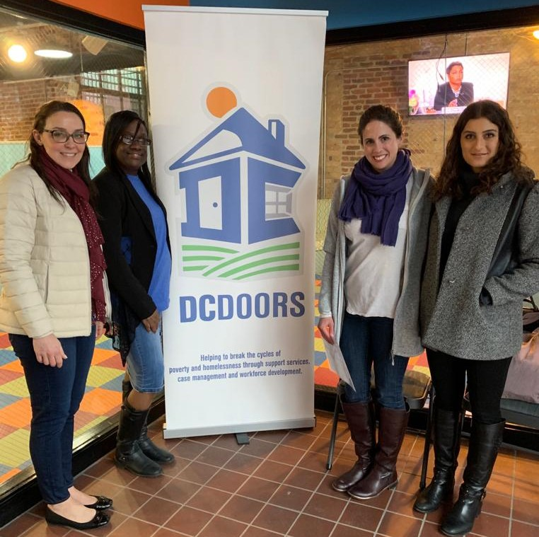 Students Yamel Sarquis Elias (G'20), Kristi Pelzel (G'20), and Brittany Panetta (G'20) standing in front of a DCDoors pull up sign