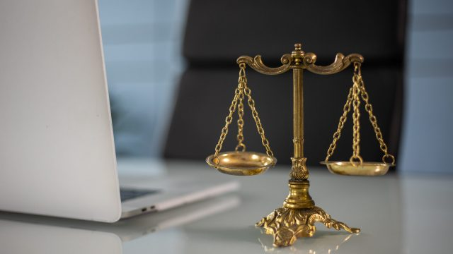 Laptop and justice scale on desk