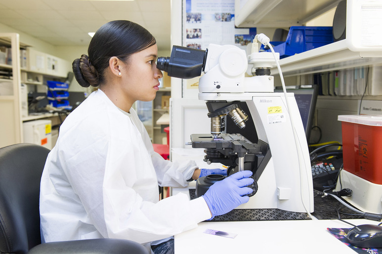 Change STEM Majors: Photo of woman dressed in a lab coat using a microscope in a laboratory